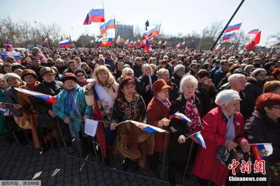 当地时间2014年3月18日,乌克兰塞瓦斯托波尔,民众聚集在广场上,观看普京就克里米亚入俄发表讲话的实况转播。3月18日,俄罗斯总统普京在克里姆林宫与克里米亚议会主席、塞瓦斯托波尔签署关于克里米亚和塞瓦斯托波尔加入俄罗斯的协议。