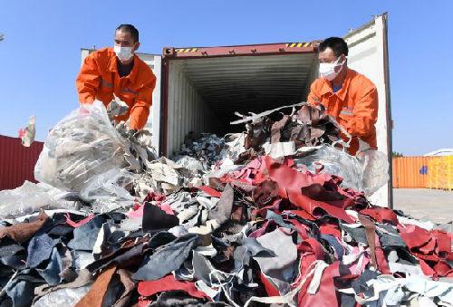 2017年12月21日,工人在厦门海关的海沧查验场清理查获的进口牛皮革洋垃圾。(新华社)