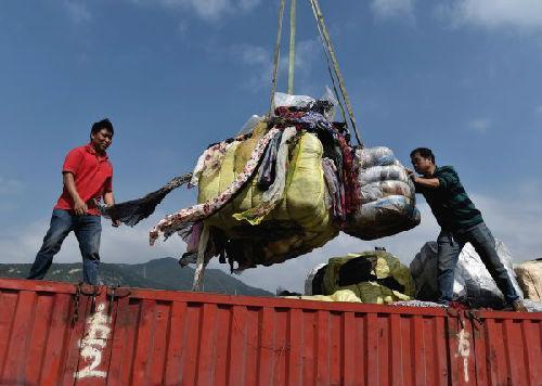 深圳土洋码头工作人员正在搬运和销毁走私废旧衣物。(新华社)