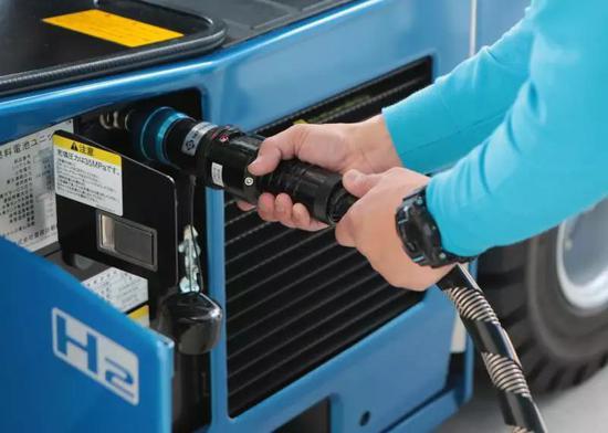 日本工作人员给氢燃料电池叉车充氢。(新华社记者马曹冉摄)
