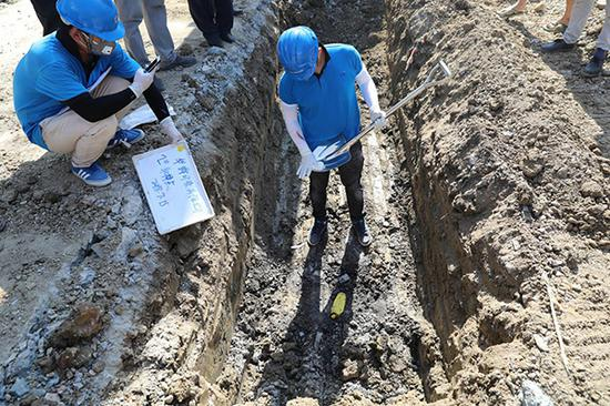 第三方检测机构工作人员对疑似掩埋化工废料处进行取样。